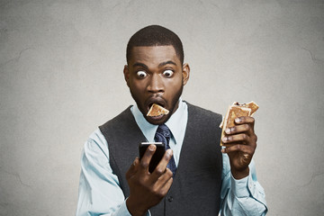 Shocked business Man reading breaking news on Phone while eating