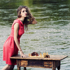 girl in a dress playing chess at a vintage table
