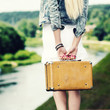 Hipster girl with vintage suitcase on the urban landscape.