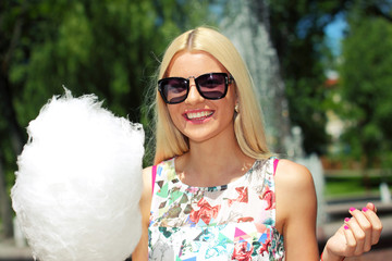 trendy girl in sunglasses  eating candy floss.