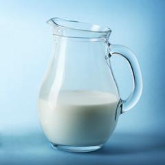 Glass jug of fresh milk on blue background
