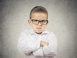 Portrait Angry, grumpy Boy with glasses on grey wall background