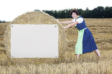 Woman rolls of straw bales with shield