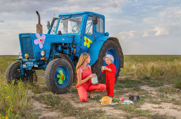 mother feeding her son tractor in a field near the tractor