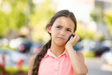 Unhappy, sad girl talking on smart phone, outside background