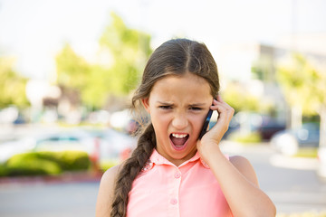 Angry child screaming on the mobile phone, outside background