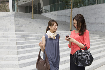 Women talk while looking at the mobile phone