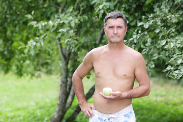 portrait of a middle-aged man with an apple in his hand on a bac