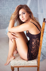 Leggy young woman sitting on a chair