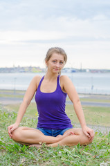 Young pretty woman meditating by the sea.