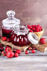 Berries jam in glass jars on table, close-up