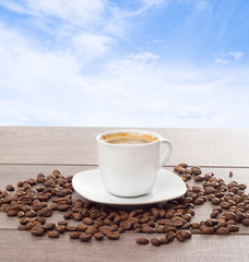 cup of coffee and coffee beans on a background of blue sky