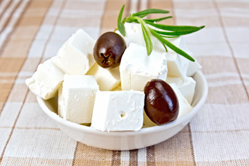 Feta with olives in cup on brown cloth