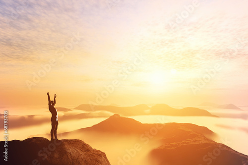 Happy man with hands up on the top of the world above clouds - 68793703