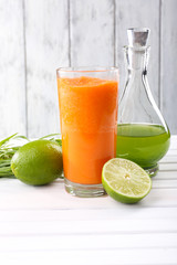 Glass of fresh carrot juice, decanter of lime juice, lime, tuft