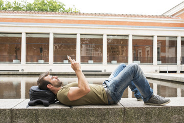 Man relaxing and looking tablet computer in the street.