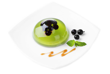 Green jelly with blackcurrant berries and sauce, isolated