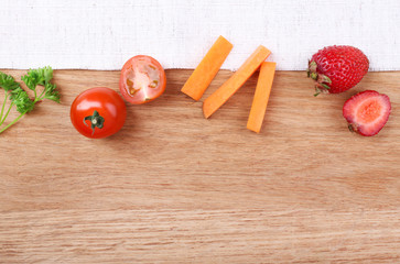 Different slices of vegetables and berries on wooden table