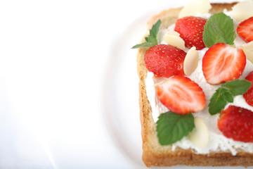 Бутерброд из белого хлеба и творожного сыра с ягодами клубники