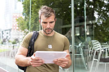 Portrait of serious urban man lwith tablet computer in the stree