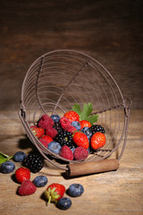Ripe sweet different berries in metal basket,