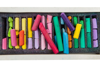 stack of multicolored pastel chalks on box isolated on white