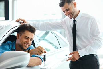 Car Salesman Handing over new Car Key to Customer at Showroom