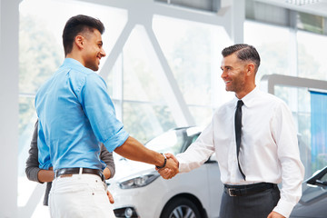 Car Showroom. Young Couple is Meeting with Seller in Auto Salon