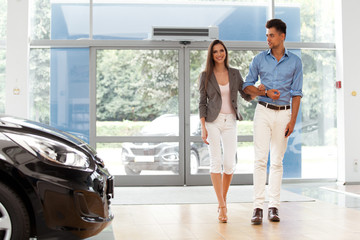 Young couple came into the car showroom