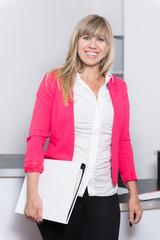 Lächelnde Frau mit Aktenordner steht im Büro