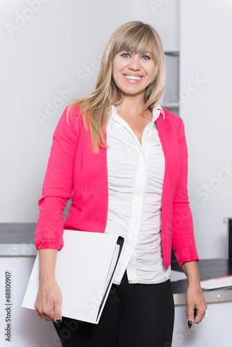 canvas print picture Lächelnde Frau mit Aktenordner steht im Büro