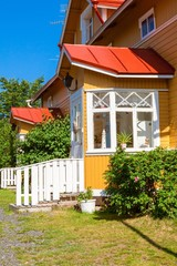 Wooden yellow house with red roof in Scandinavian style