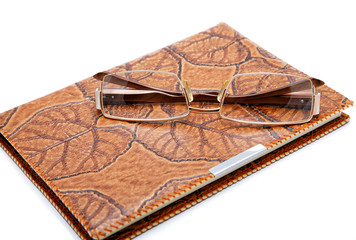 Leather  notebook and glasses isolated on a white background