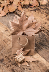 gift, shopping bag and dried leafs on wooden surface