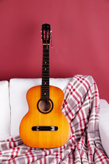 Guitar on a big white sofa on white background