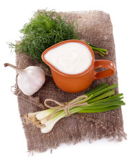 Clay pot with cream and a tuft of onion, dill and garlic near