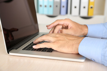 Man working on laptop on wooden table on folder background