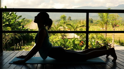 Silhouette of woman exercising, stretching back on terrace