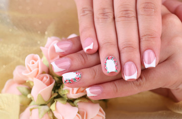 Female hand with stylish colorful nails  with decorative flower