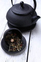 Black teapot, bowl and tea on color wooden background