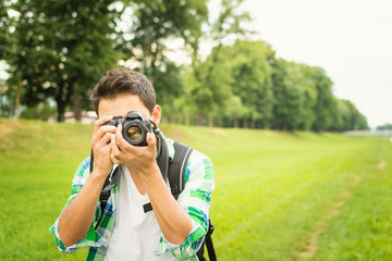 Young hipster man with digital camera outdoors