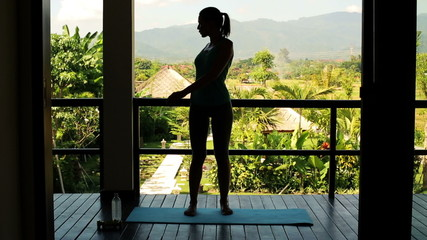 Silhouette of woman warming up before exercise on terrace