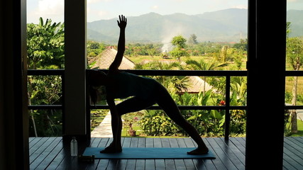 Silhouette of woman doing yoga pose on terrace