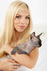 Beautiful young woman with gray sphinx cat sitting on bed