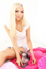 Beautiful young woman with gray sphinx cat sitting