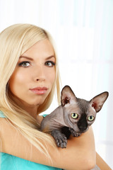 Beautiful young woman holding gray sphinx cat