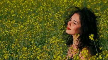 Ecology. Thoughtful woman is in a field of Raps.