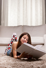 young girl reading a big book on her living room