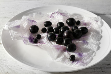 Purple grapes on plate on wooden background