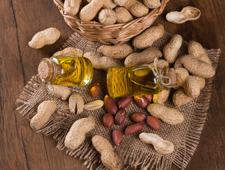 Peanut oil in a glass bottle with raw peanuts